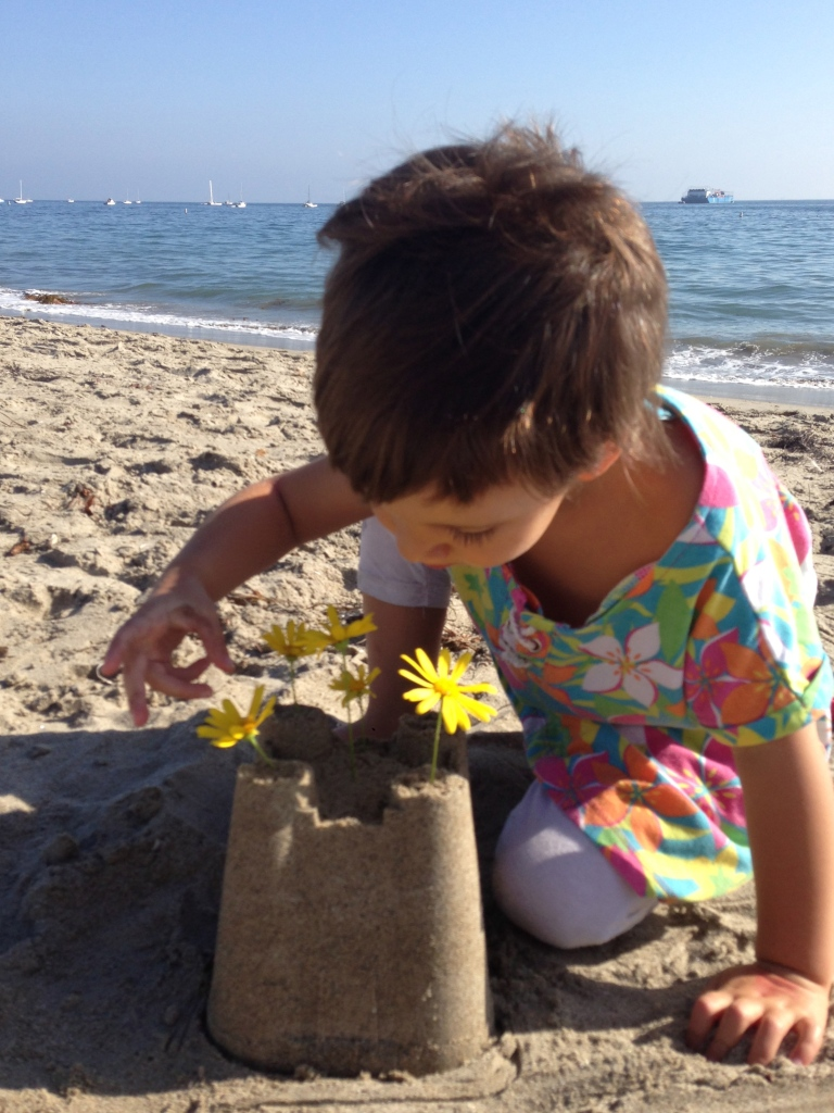 Miss 3 and her sand flower castle