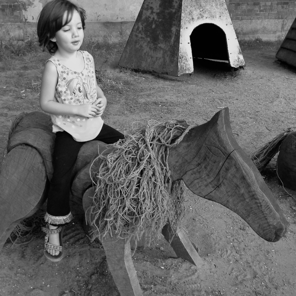 Miss 4 rides a wooden horse on an imaginary adventure