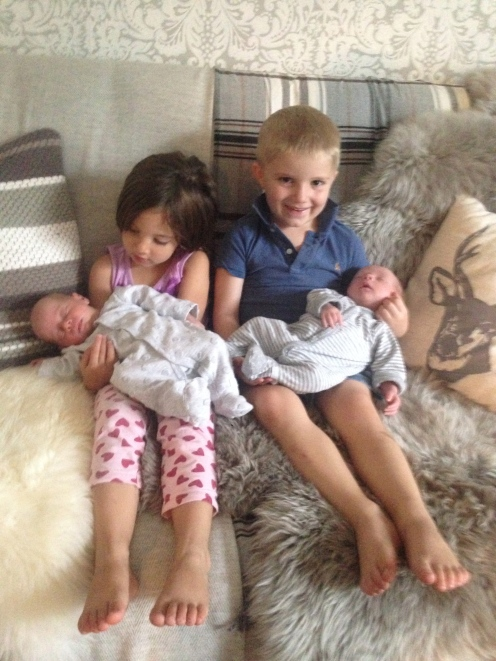 Our Miss 4 with friend's 4 year old, each holding a 4 week old baby - twins! Boy and girl.
